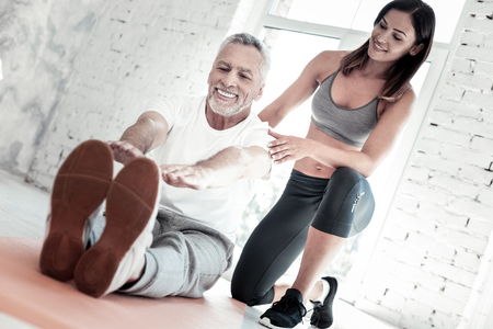 So much better. Low angle shot of an extremely happy senior man getting excited while listening to his coach and stretching at a gym. Stock Photo