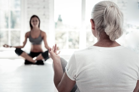 Getting much better. Retired lady with a ponytail sitting in a lotus position and calming down during a yoga session. Stock Photo