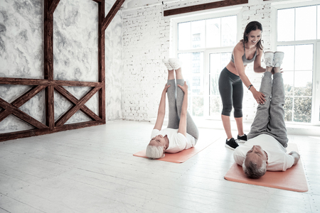 Do not sit be active. Sporty senior woman and man lying on their fitness mats and lifting their legs while exercising in a gym.