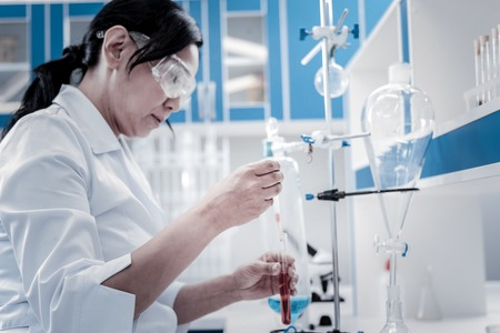 Experimental approach. Selective focus on a hand of a female chemist wearing safety glasses and a labcoat while working in a laboratory and conducting a chemical experiment. Stock Photo