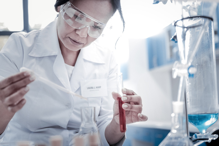 Future breakthrough. Selective focus on a concentrated chemist holding a pipette and pouring a liquid into a flask while conducting a chemical experiment.