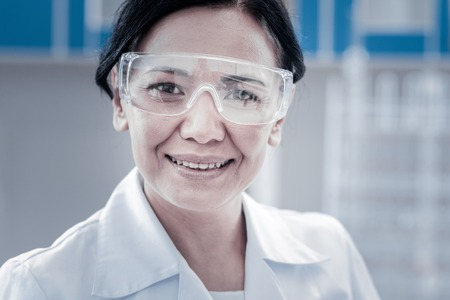 Do what I love and love what I do. Portrait of a positive minded scientist wearing safety glasses posing for the camera with a joyful smile on her face while working in a laboratory. Stock Photo