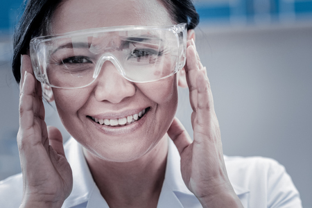 Positive attitude to work. Close up portrait of a cheerful female researcher grinning broadly while looking into the camera and touching her safety glasses in a lab. Stock Photo