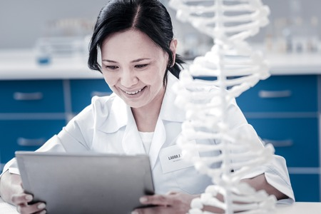 Innovative approach. Positive minded mature lady smiling while sitting next to a DNA model and working on a touchpad in a lab.