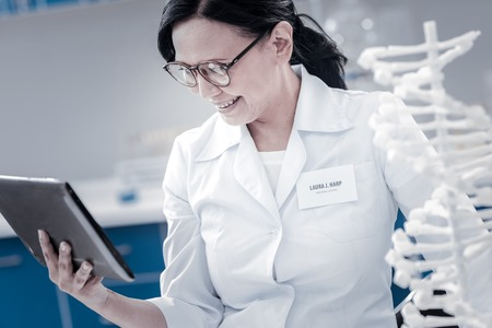 Relaxing workspace. Happy female scientist wearing glasses standing at a DNA model and grinning broadly while focusing her attention on a screen on a tablet computer.