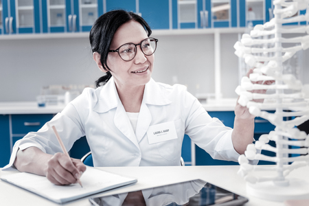 Motivated mature woman smiling while analyzing a three dimensional model of DNA and taking some notes in a notebook in a lab. Stock Photo