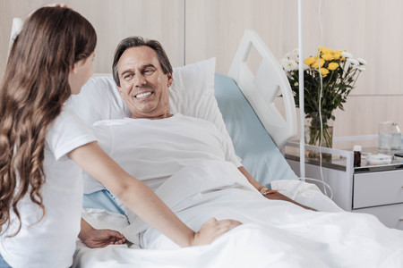 I believe in you daddy. Selective focus on a radiant gentleman lying in a hospital bed and grinning broadly during her daughter visit.