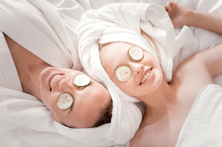 Fresh look. Happy nice positive mother and daughter lying together and smiling while doing a cucumber mask