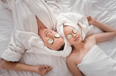 Pleasant activity. Nice happy positive mother and daughter lying together and relaxing while doing a cucumber mask