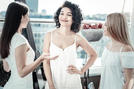 Temps libre. Joyeuses femmes positives positives souriant et debout dans le cercle tout en profitant de leur réunion