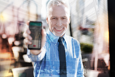 Amazing gadget. Emotional positive mature businessman feeling excited and smiling while standing in a lovely cafe and demonstrating his new wonderful modern smartphone Stock Photo