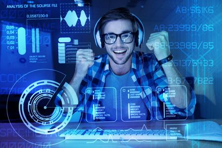 Bien hecho. Programador joven emocional positivo que se siente feliz mientras está sentado frente a una pantalla transparente moderna después de crear un programa importante para proteger los datos personales