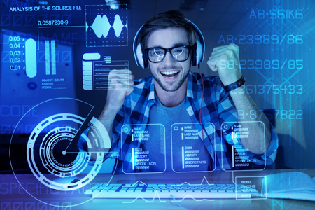 Well done. Positive emotional young programmer feeling happy while sitting in front of a modern transparent screen after creating an important program for protecting personal data