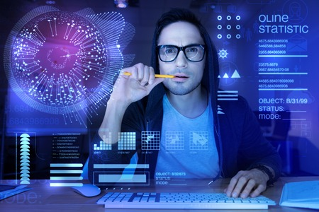 Clever experienced qualified programmer looking at the transparent screen of his modern device and frowning while biting his pencil Stock Photo