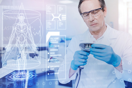 Calm clever experienced doctor feeling concentrated while standing with a new tool in his hands and trying to use it Stock Photo