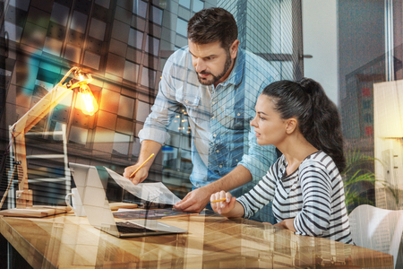 Clever enthusiastic young coworkers feeling interested while sitting in front of a modern laptop and looking at the screen of it