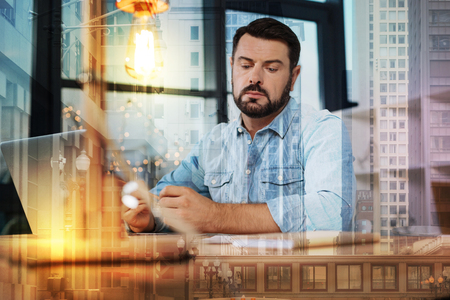 Unusual idea. Calm curious thoughtful man looking attentively at the documents on the table while sitting at home in front of a modern laptop Stock Photo