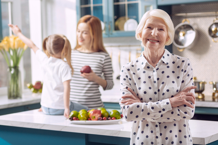 In peace. Pleasant cheerful elderly woman folding her hands across her chest and posing in the kitchen while her daughter gives an apple to the kid Stock fotó