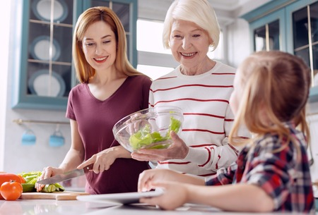 Vital girl. Caring little girl sitting at the kitchen counter and prompting next steps in salads making for her mother and grandmother while consulting the tablet