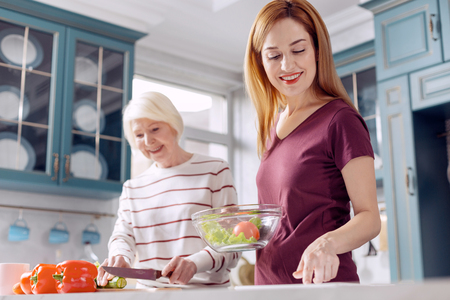Healthy dish. Charming young woman and her elderly mother making a salad together, the younger woman holding a bowl with vegetables while the older one cutting Stock Photo
