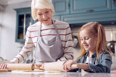 Cooking lessons. Charming little girl standing next to her grandmother and rolling out dough together with her, following her example