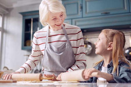 Important lesson. Happy senior woman in an apron explaining her little granddaughter how to roll out dough while smiling at her lovingly