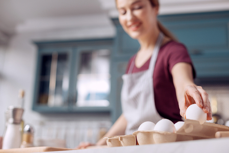 Indispensable ingredient. The focus being on the hand of a charming young woman in an apron taking an egg from an egg carton while making dough for cookies Stock Photo