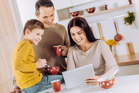 Pleasant breakfast. Upbeat young family having breakfast in the kitchen and watching a video on tablet together while laughing amusingly