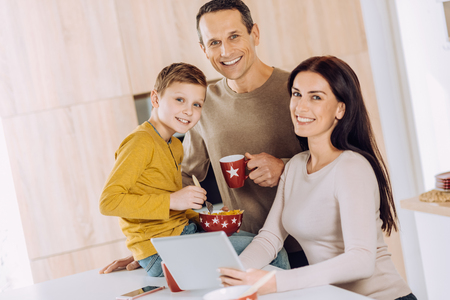 Idyllic morning. Pleasant cheerful young family posing for the camera while having breakfast and watching a video on the tablet Stock Photo