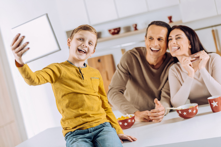 Precious moment. Joyful little boy sitting on the kitchen counter and taking a selfie of himself and his parents with a tablet while they posing funnily