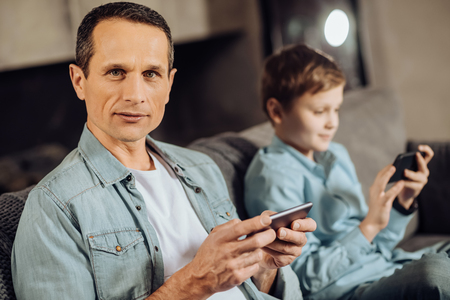 Avid gamer. Handsome pleasant man sitting on the sofa next to his pre-teen son and posing for the camera while playing on his phone, the boy doing the same Stock Photo