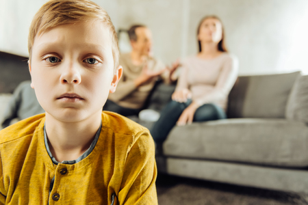 All alone. The focus being on the upset little boy feeling lonely and looking sadly at the camera while his parents sitting on the couch and quarrelling in the background Stock Photo