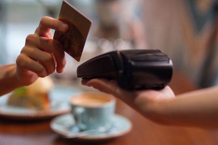 Credit card usage. Moment of payment with a credit card hold by female hand through terminal which carried by another hand Archivio Fotografico