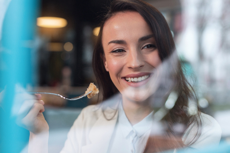 Snow white smile. Cheerful attractive sincere woman smiling while carrying fork and posing on the blurred background