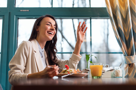 Bill please. Joyful good looking young woman tasting salad while rising hand and laughing