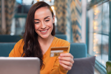 Pay anywhere. Pretty joyful merry woman using credit card while gazing down and grinning Stock Photo