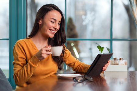 Online call. Optimistic cute merry woman drinking tea while carrying tablet and smiling Stock Photo
