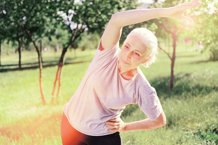 Constantly training. Waist up of serious elderly woman doing exercises outdoors while expressing calmness