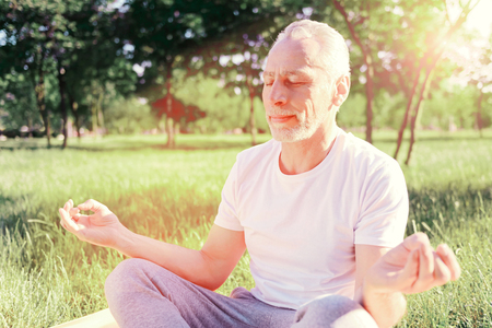 Calmness. Close up of peaceful man keeping fingers together while sitting on the ground pad and doing yoga