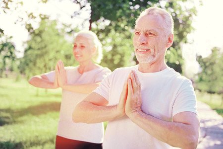 Mental equilibrium. Close up of smiling friends doing yoga in fresh air while looking away and expressing interest