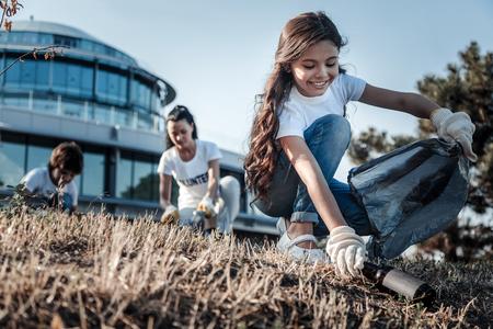 To śmieci. Śliczna pozytywna wesoła dziewczyna podnosi butelkę i uśmiecha się, pomagając jednocześnie chronić środowisko