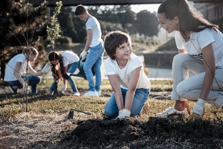 Young environmentalist. Cheerful nice positive woman looking at the boy and smiling while helping him to plant a tree