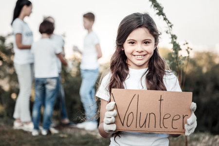 Helping people. Happy positive cute girl smiling and looking at you while being a volunteer Zdjęcie Seryjne