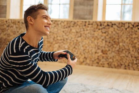 My favourite game. Good-looking exuberant fair-haired young man smiling and holding a remote control for games while sitting on the floor