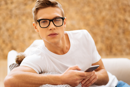 Unlucky day. Attractive worried unsmiling young man wearing glasses and holding his phone and feeling sad