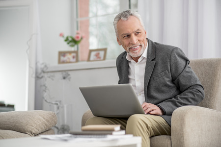 Have idea. Handsome bearded man keeping smile on his face and looking aside while holding laptop on knees