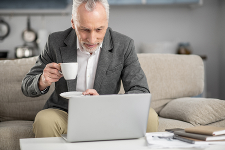 Checking mail. Concentrated gray-haired man bowing head and holding cup while looking at computer
