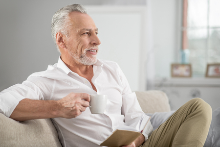 Coffee break. Attractive mature man keeping smile on his face and holding cup in right hand while having dreamy mood