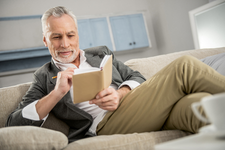 Positive worker. Cheerful male person keeping smile on his face and holding notebook while sitting on the sofa 스톡 콘텐츠