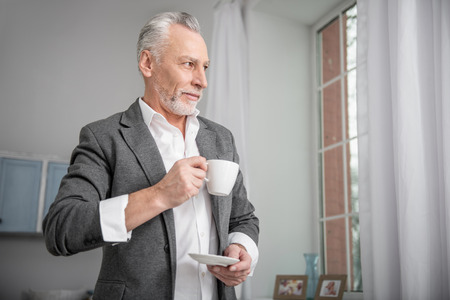 Think a little. Concentrated retirement turning head while holding cup in right hand and enjoying his break 스톡 콘텐츠